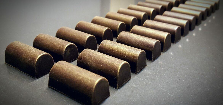 Doppia fila di cioccolatini su piano di metallo